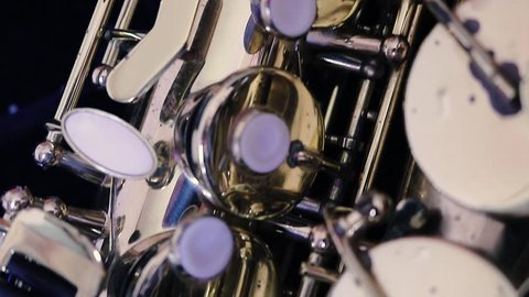 Details of a golden saxophone. A wind instrument seen very close to the camera.