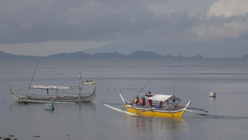 Local boat carefully leaving harbour with small canoe in background and passing an unmanned boat to its port side