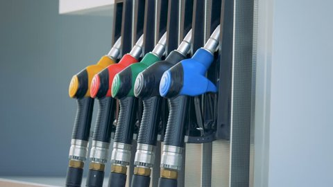 Male hand is taking out a green petrol nozzle from the pump. Gasoline fuel, gas station concept.