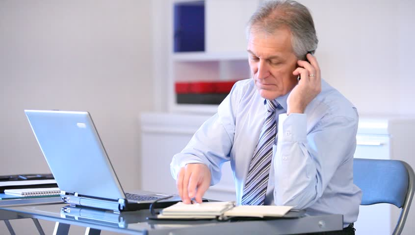 Senior businessman talking on the phone in office