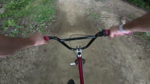 Extreme sports POV BMX rider on dirt jump trails bike tricks