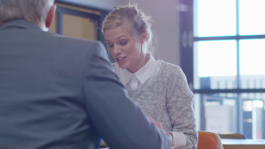 Handheld shot of businesswoman using mobile phone while discussing with male colleagues in office