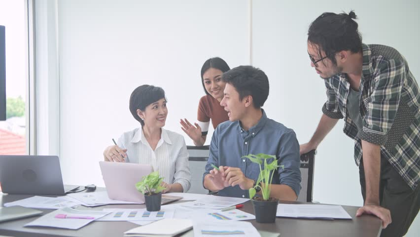 Business meeting. Small start up business meeting in room. Young Asian man presenting his idea to his team sitting together. New business model start up concepts. | Shutterstock HD Video #1016216374