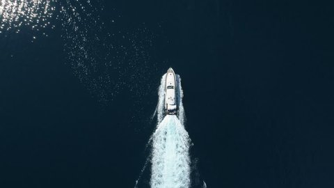 Aerial - Top down view of luxury motor boat racing on the water
