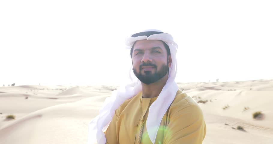 Arabian man with traditional emirates clothes walking on the Dubai desert. Different poses and expressions. Wearing yellow kandura