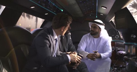 Business team at work, three men in the limousine speaking and making plans about future investments