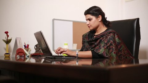 An Indian Business Women having water while working on her laptop at an office in New Delhi, India