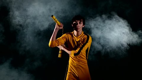 The man in  yellow suit practicing kung fu. Master holding nunchuck. Fighter isolated on black background. Concept of healthy life and martial arts. smoke. Bruce Lee style.
