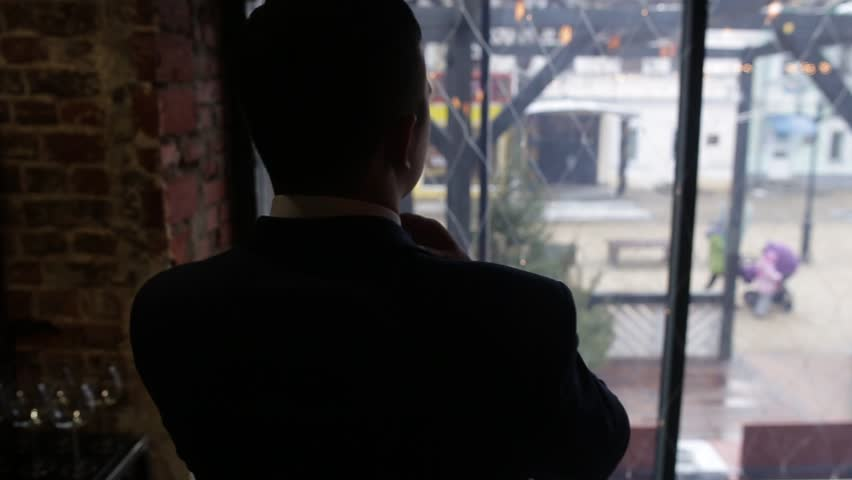 Businessman thinking in office, looking out of windows to downtown vista. Back view of a successful boss looking through a window, while is standing in his modern office. Young man skilled | Shutterstock HD Video #1016261014