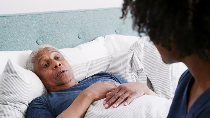 Nurse Visiting Senior Man Lying In Bed Suffering With Illness | Shutterstock HD Video #1016267584