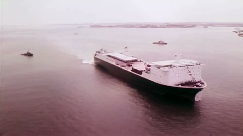 CIRCA 1970s - A container ship and a tugboat are shown in transit in New York Harbor.