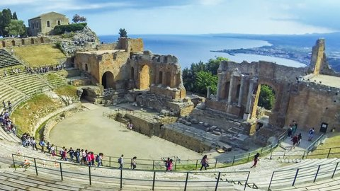 TAORMINA, ITALY - MAY 15, 2018: Ruins of ancient Greek theater in Taormina, famous resort in Sicily, Italy. Coast of Giardini-Naxos bay of Ionian sea and Mount Etna in smoke on background. Time Lapse