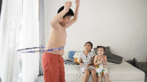 Fat boy playing hula hoop at home, slow motion with belly moving.  His sisters cheer up for exercise.