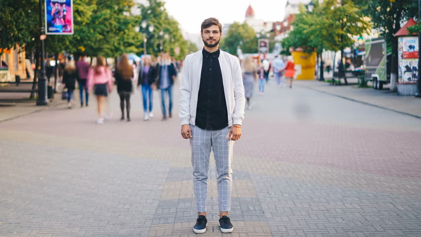 Zoom in time-lapse of young businessman in trendy garments standing in pedestrian street and looking at camera while crowds of people are whizzing around. | Shutterstock HD Video #1016357194