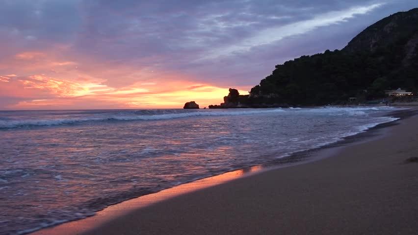 Purple and orange sunset sky reflected on sand and water in Pelekas beach, Corfu, Greece