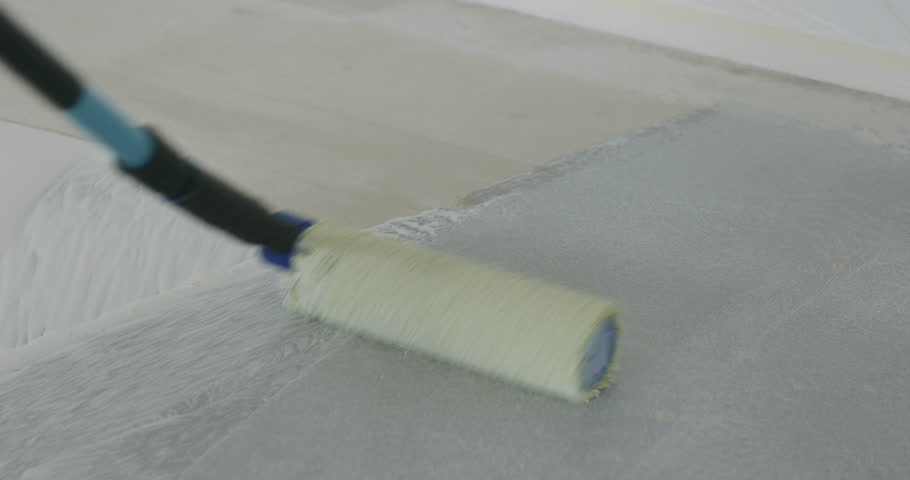 Slow motion pan applying primer on the floor