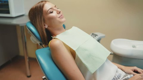 Happy smile of girl with orthodontic braces in dental chair. 4K.