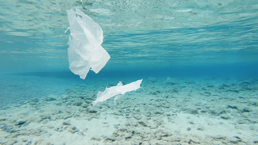 Sea Pollution by Plastic. Pieces Of Plastic Foil Floating Underwater Close To The Surface