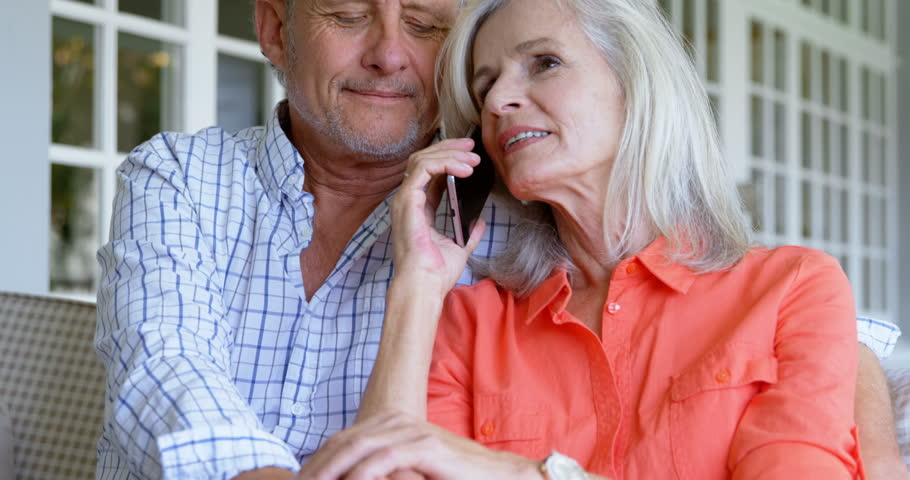 Front view close up of senior Caucasian woman talking on mobile phone next to her man on sofa at home