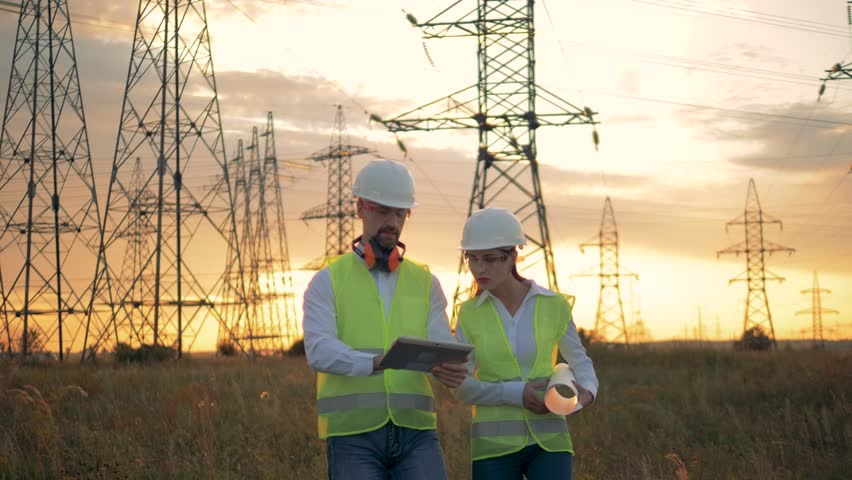 Professional engineers walking through a field near electrical line.