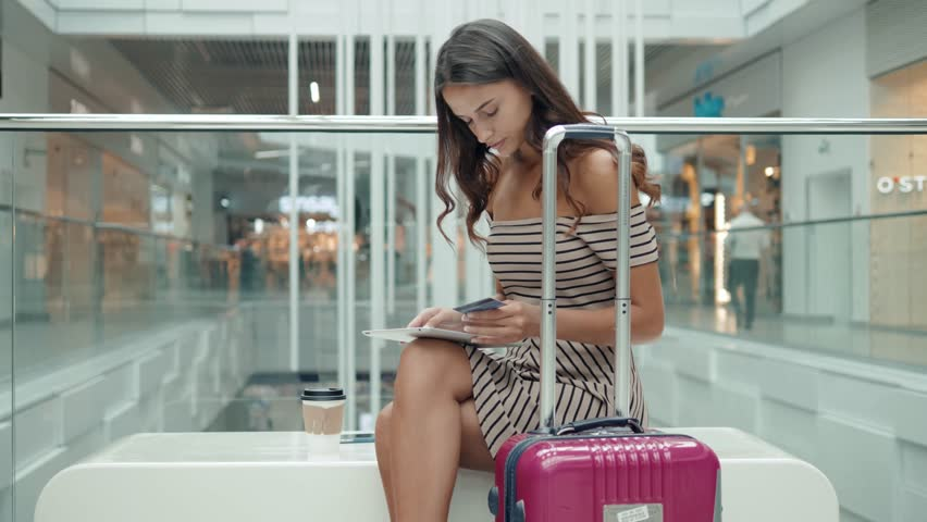 pretty woman tourist happy brunette girl shopping online with credit card and tablet in airport terminal shopping mall bench nfc baggage suitcase booking hotel or room flat