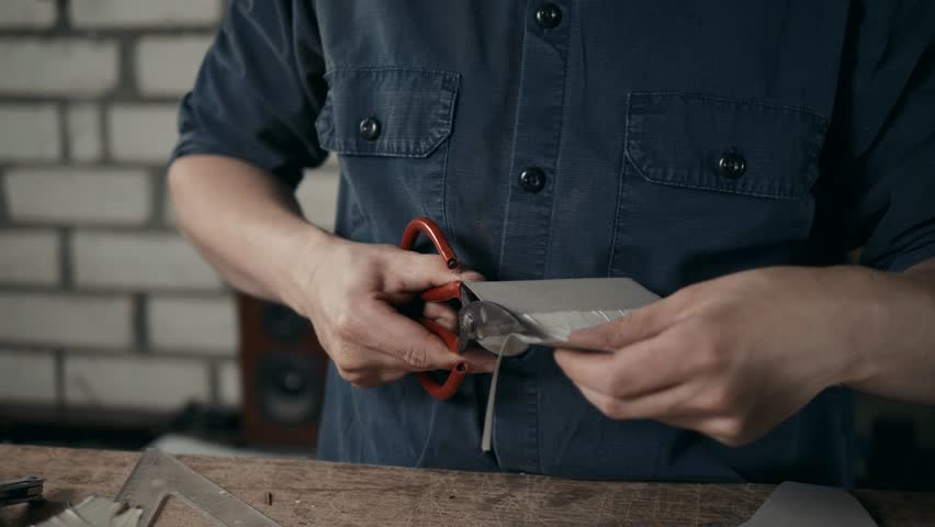Man working with leather using crafting DIY tools scissors shoemaker boots shoes working
