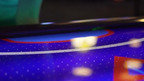 Slo-motion, side shot of a hand placing a puck on an air hockey onto the table and hitting it around the table.