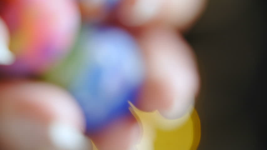 Colorful marbles roll off the person hands macro shot 4K. Long shot of a pile of marble balls in person's hand in focus while roll out of the frame.