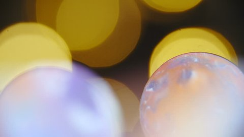 Slide over colorful planets shaped marbles macro shot 4K. Long shot dolly zoom-out with refocusing over colorful marbles and stopping at the single one.