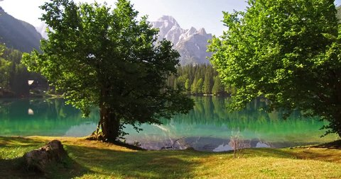 Stunnig summer view of Fusine lake. Amazing morning scene of Julian Alps with Mangart peak on background, Province of Udine, Italy, Europe. 4K video (Ultra High Definition).