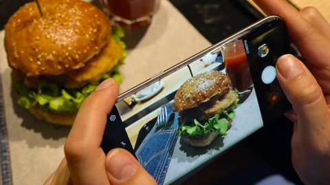 Girl makes a photo of burger and tomato juice on a smartphone in a cafe close up
