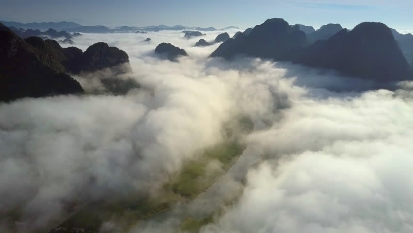 Pictorial picture drone flies over valley river covered with thick fog and  protruding endless mountains at sunrise | Shutterstock HD Video #1016599804