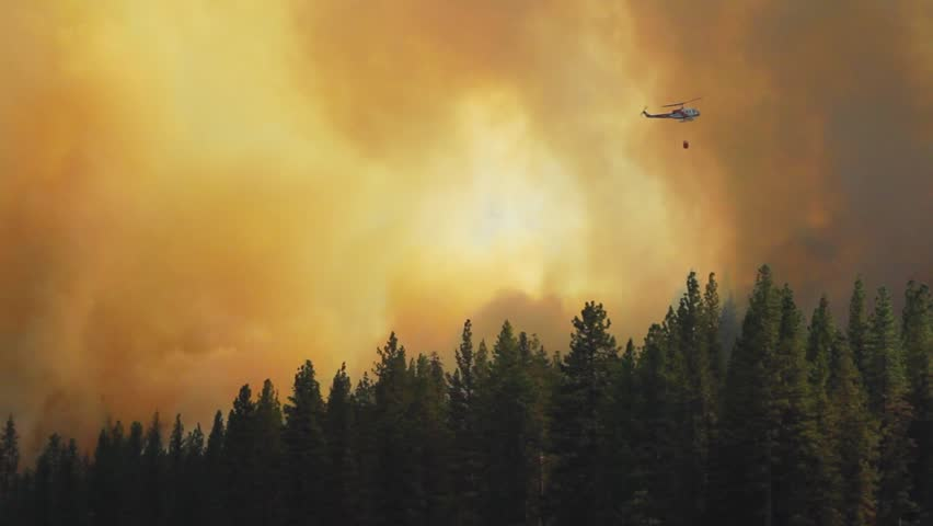 Helicopter dropping water on raging fire in California mountains.