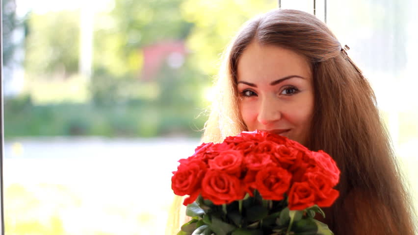 Portrait of a young beautiful woman with a bouquet of flowers of red roses. #1016677204