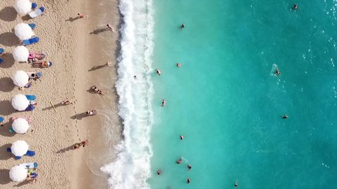 Aerial top view video of tropical sandy exotic emerald paradise sandy crowded beach with sunbeds and umbrellas