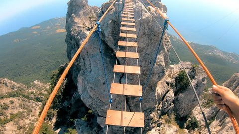 The rope bridge. Crossing over a suspension bridge in the mountains. Extreme sport. GoPro.