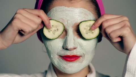 Close up of a girl with a face mask and a towel on her head that closes her eyes with cucumbers on a gray background. Face care concept. Beautiful girl with cosmetic mask on her face