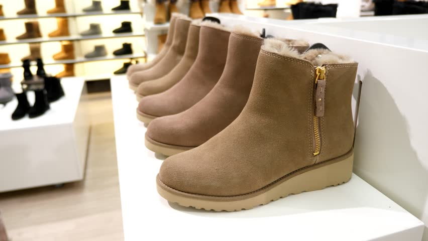 Warm shoes on rack at footwear store, winter season collection. Sheepskin boots with ankle height for women, other colours seen at racks, blurred on background