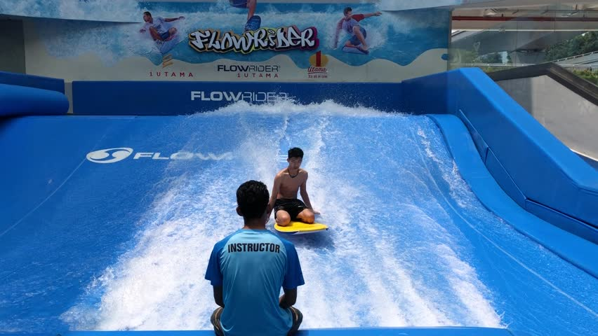 Kuala Lumpur, Malaysia - September 20 2018: Kids and an instructor at an indoor surfing facility, Flow Rider in a shopping complex, One Utama, Damansara.  | Shutterstock HD Video #1016749354