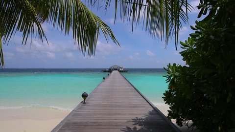 Long wooden pier leading from tropical forest in inland to private water villas and jetty with a boat. On the Maldives.
