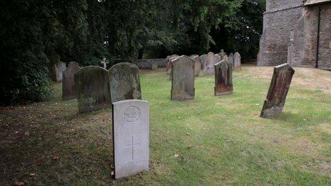 Gravestones in an English churchyard under a yew tree SLIDER SHOT