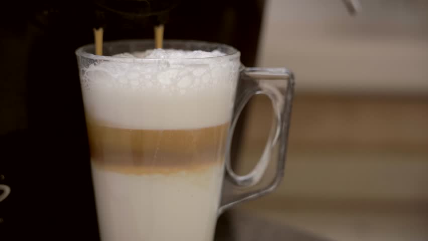 Close-up of espresso pouring from coffee machine. Professional coffee brewing. Making a caffe latte coffee.