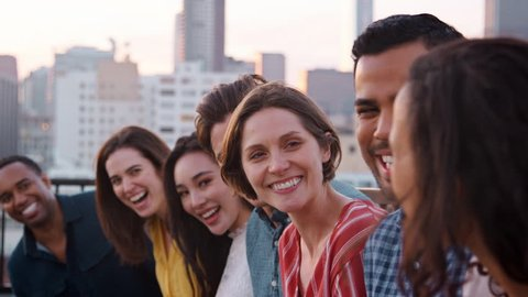 Friends Standing In A Line Gathered On Rooftop Terrace For Party With City Skyline In Background
