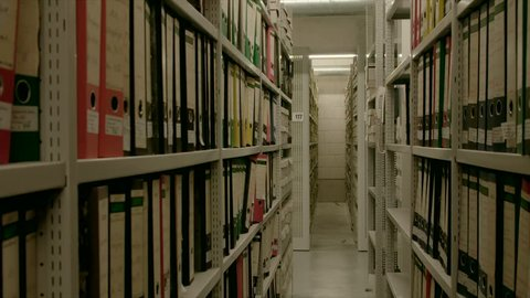 In an archive, between two shelf walls, the camera moves out. The image can be used for the integration of archive texts in films and reports. Thanks to the 50 frames it can be slowed down.