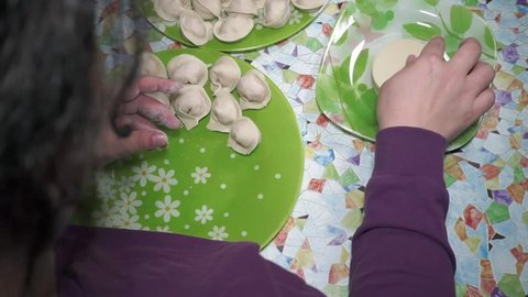 A woman is making pelmeni. Chinese dumplings stuffed with minced meat and vegetables. View from the back from above.