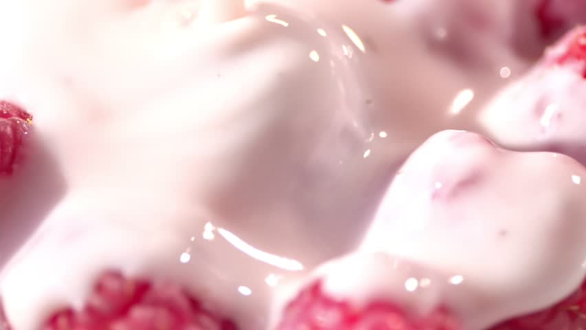 High angle stream of viscous fresh yogurt or milk or cream pouring into red ripe berries close-up   Shutterstock HD Video #1016828794