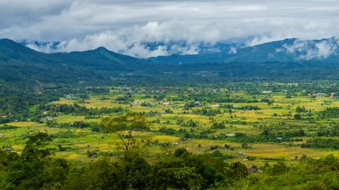 Beautiful View of a Green Valley Landscape with Fast Rolling Clouds Drifting Over Mountains at the horizon.  Soft Focus,Time lapse. Borneo Sabah, Malaysia. 4K UHD.