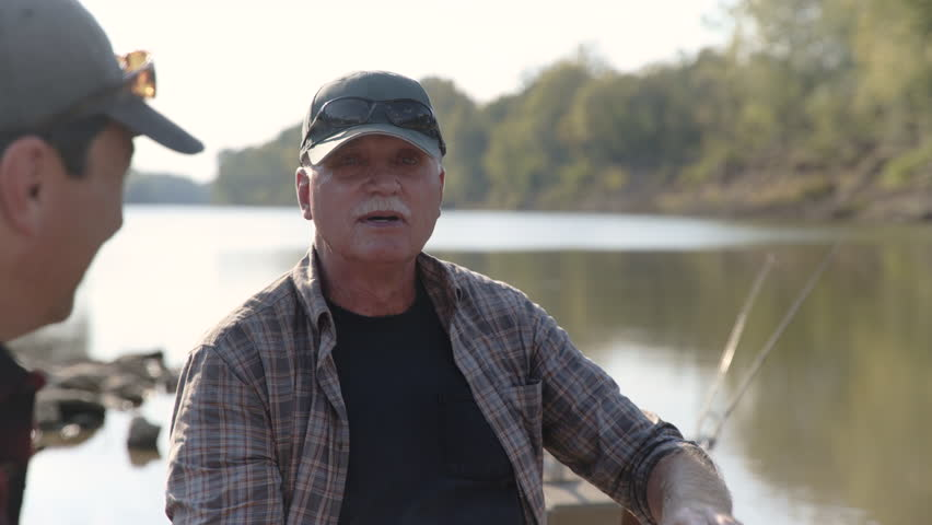Dolly shot of happy senior father talking to mature son while sitting on boat at lakeshore | Shutterstock HD Video #1016891104