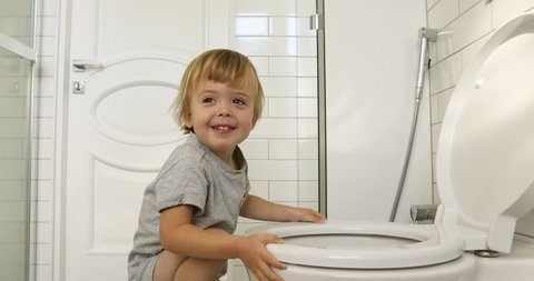 Kid boy climbs on the toilet, prepares to makes to toilet the white interior bathroom