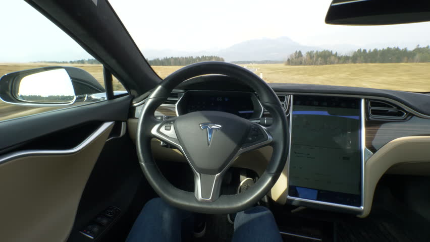 TESLA AUTONOMOUS CAR, March 2018 - POV: Young woman cruises down an empty country road in a self steering Tesla car. Sunny rural landscape surrounds the autonomous vehicle driving down the road. | Shutterstock HD Video #1016921014